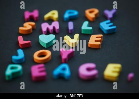 Mots multicolores AMOUR SOURIRE HEUREUX DE LA JOIE ET DE LA PAIX avec une forme de coeur sur fond noir Banque D'Images
