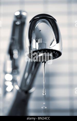 L'eau qui goutte du robinet de cuisine en acier inoxydable Banque D'Images