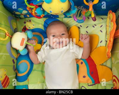 Happy smiling six semaine mignon bébé garçon couché dans un joli tapis de jeu avec des jouets Banque D'Images