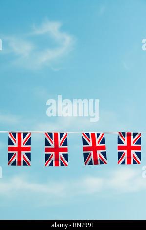 Union Jack flag bunting against a blue sky Banque D'Images