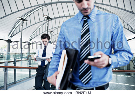 Businessman text messaging on cell phone Banque D'Images