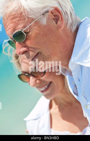 Happy senior man and woman couple ensemble face à la mer sur une plage tropicale déserte Banque D'Images