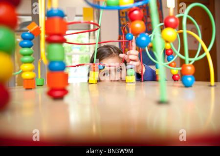 Jeune fille jouant avec un jouet éducatif Banque D'Images