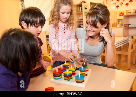 Enseignant de maternelle enfants qui jouent Banque D'Images