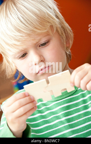 Jeune garçon tenant deux pièces de puzzle, low angle view Banque D'Images
