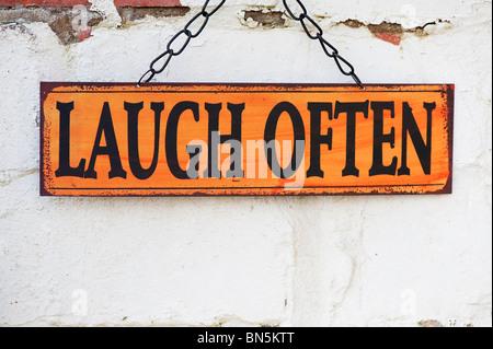 Rire souvent. Vieux Jardin métal signes sur un mur de brique peint Banque D'Images