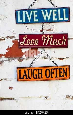 Vivre, aimer, rire, vieux métal jardin signes sur un mur de brique peint Banque D'Images