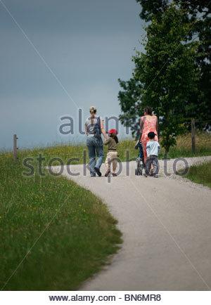 Deux femmes avec leurs fils marcher le long d'un chemin escarpé dans un champ d'herbe Banque D'Images