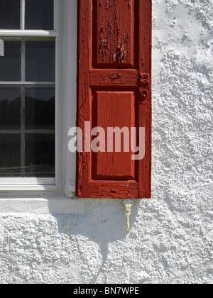 Fenêtre d'obturation, le rouge et blanc mur en stuc, New York USA Banque D'Images