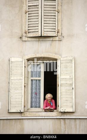 Une vieille femme regardant par la fenêtre d'un immeuble ancien, Nancy, France Banque D'Images