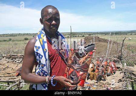 Un villageois Masai montrant les travaux d'artisanat traditionnel il y a sur l'affichage dans le village à l'intérieur Banque D'Images