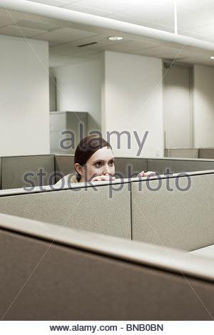 Femme de se cacher derrière le bureau dans l'armoire Banque D'Images