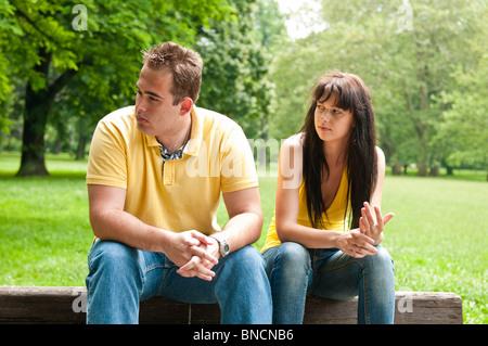 Jeune couple assis sur un banc à l'extérieur ayant des problèmes relationnels Banque D'Images