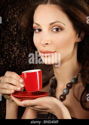 Belle Jeune femme tenant une tasse de café espresso rouge avec des haricots de café derrière elle en arrière-plan Banque D'Images