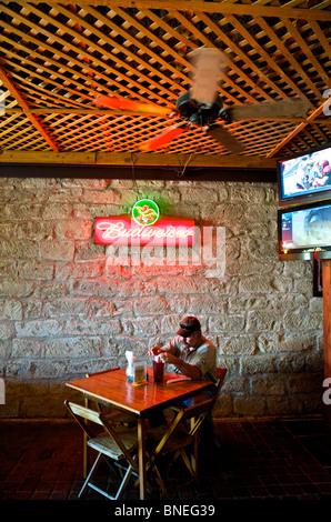 Un homme assis seul dans le restaurant Biergarten Auslander et Hill Country Fredericksburg, au Texas, USA
