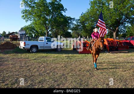 Cowgirl waving flag en bestiaux avant la cérémonie d'ouverture de l'érythroblastopénie événement rodéo au Texas, USA