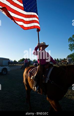 Cowgirl en agitant le drapeau américain à la cérémonie d'ouverture de l'érythroblastopénie événement rodéo au Texas, USA