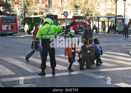 """Un """"agent de Movilidad' mobilité (agent de police) aide un groupe d'école 8 enfants à traverser la rue Calle de Banque D'Images"""