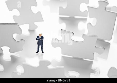 Figurine homme entouré par des pièces de puzzle Banque D'Images