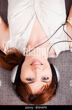 Vue de dessus d'une belle jeune femme à l'écoute de la musique avec des écouteurs Banque D'Images