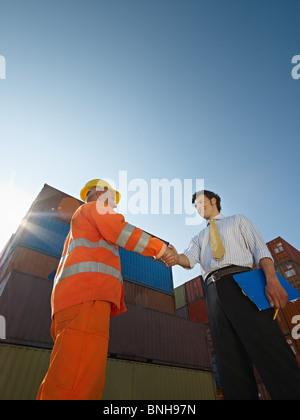 Employée de bureau et d'ouvrier se serrer la main près de conteneurs de fret