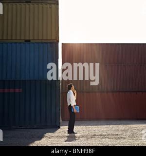 Mid adult businessman standing près de conteneur et en haut. Banque D'Images