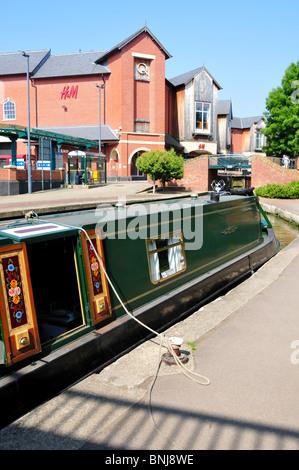15-04 amarré sur le canal d'Oxford à Banbury avec Castle Quay Shopping Centre à l'arrière Banque D'Images