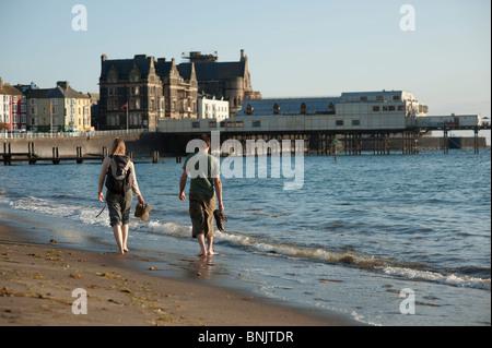 Un jeune couple en train de marcher le long de la plage à Aberystwyth, Pays de Galles UK un soir d'été Banque D'Images
