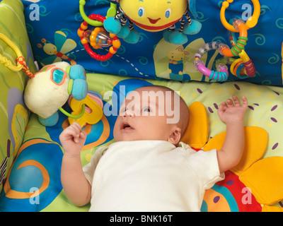 Six semaine mignon bébé garçon couché dans un joli tapis de jeu avec des jouets Banque D'Images