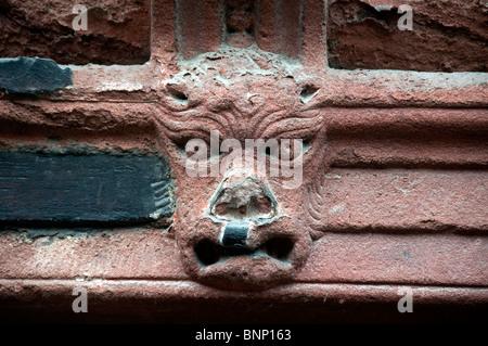 Une tête de gargouille sculptée en pierre sur une maison dans la région de Cumbria