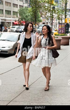 Deux jeunes femmes asiatiques chic élégant dans des vêtements d'été chat tout en flânant sur les trottoirs de Manhattan Banque D'Images