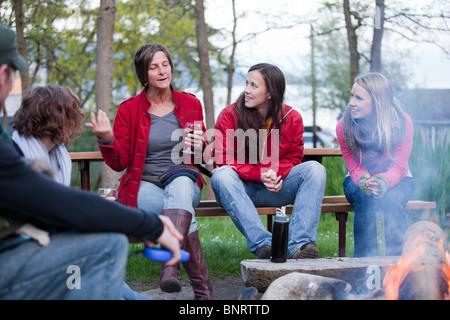 Un groupe d'amis s'asseoir et profiter des boissons tout en parlant autour d'un feu de camp. Banque D'Images