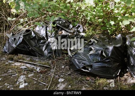 Déchets d'amiante dans des sacs en plastique dans les hedge funds à côte d'une route Banque D'Images