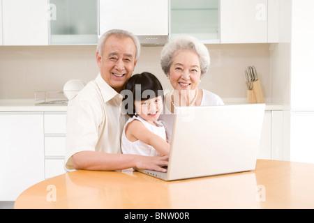 Petite fille à l'aide d'un ordinateur portable avec ses grands-parents Banque D'Images