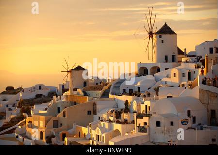 Oia ( Ia ) Santorin moulins à vent et ville au coucher du soleil, île de Thira, îles grecques Cyclades Banque D'Images