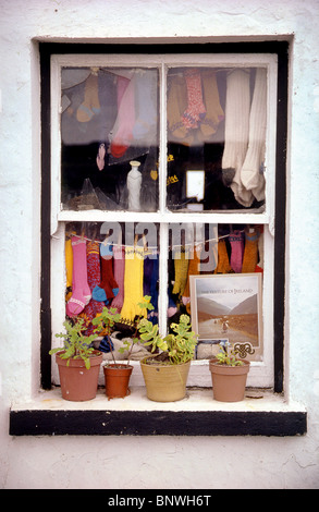 Localement colorés-chaussettes en laine tricotées sont exposés à la vente dans la fenêtre d'une maison sur l'un Banque D'Images