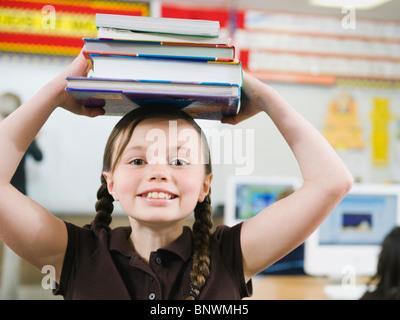 Elementary Student holding une pile de livres sur la tête. Banque D'Images
