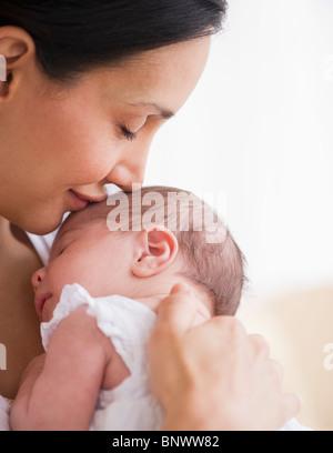 Mère embrassant la tête de bébé Banque D'Images
