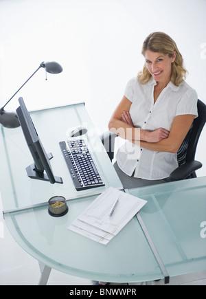 Confident businesswoman sitting at bureau moderne Banque D'Images