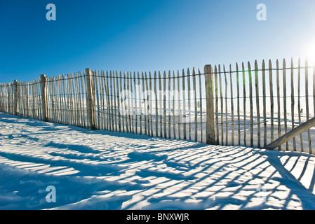 Clôture en bois dans le champ couvert de neige