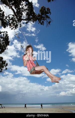Jeune fille sur Rope Swing sous Arbre Pohutukawa, Waihi Beach, Coromandel, île du Nord, Nouvelle-Zélande Banque D'Images