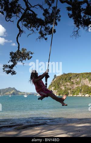 Jeune fille sur Rope Swing sous Arbre Pohutukawa, Flaxmill Bay, Coromandel, île du Nord, Nouvelle-Zélande Banque D'Images