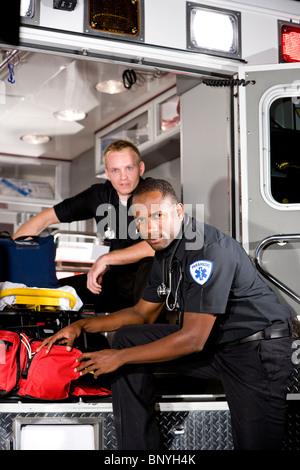 Les paramédics multiraciale de la préparation de matériel médical en ambulance Banque D'Images