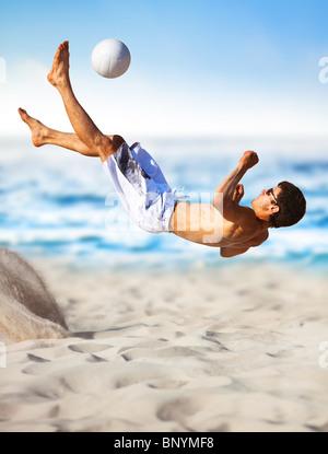 Jeune homme jouant au football sur la plage. Banque D'Images