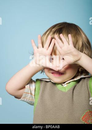 Petit garçon aux mains covering face Banque D'Images