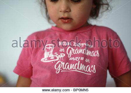Un gros plan d'une fillette de deux ans portant une chemise qui lit 'ce qui se passe chez votre grand-mère, reste Banque D'Images