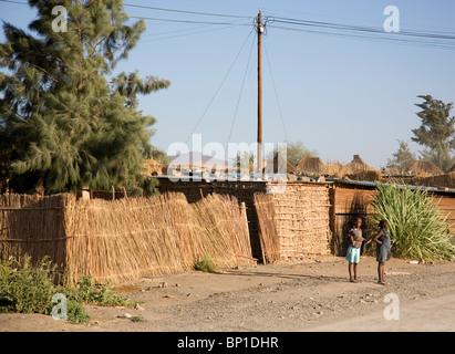 Deux filles, une avec bébé sur le dos, debout par route dans Aussenkehr Village - Namibie Banque D'Images