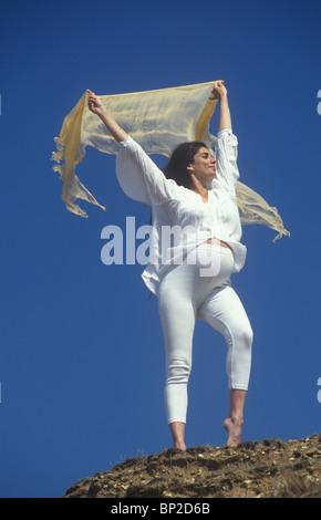 Mixed Race woman enceinte debout sur une colline qui s'étend Banque D'Images