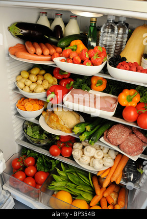 Vue à l'intérieur de réfrigérateur avec des étagères remplies de produits frais Banque D'Images