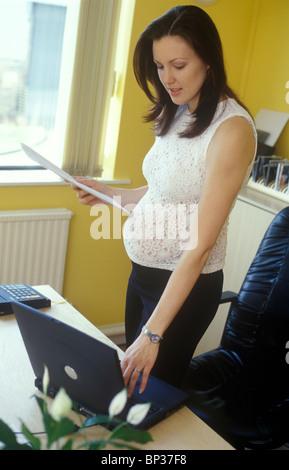 Femme enceinte fortement de travailler sur un ordinateur portable debout montrant une mauvaise posture Banque D'Images